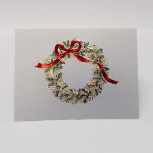Paula Skene Designs Christmas card featuring green and gold wreath with a red ribbon on brushed silver card stock