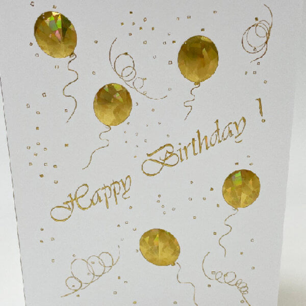 Happy Birthday gold balloons on white card closeup pixels